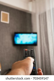 TV remote control in man's hand. In first person point of view
