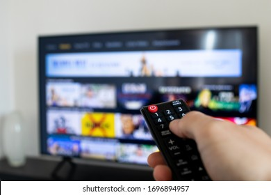 Tv remote controller in hand of customer looking for some content in Smart Tv app for streaming video. Watching streaming services for entertainment on television. Choosing TV series and movies