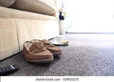 TV remote, slippers, tea and biscuits or cookies in a comfortable living room. Space for copy text.