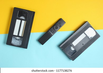 Tv remote and video cassettes on a colored pastel background Top view, minimalism