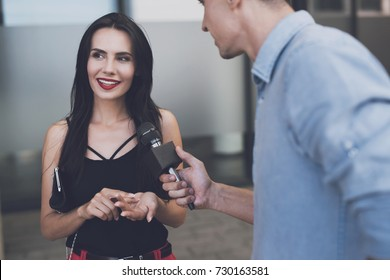 TV reporter at work. A beautiful girl smiles thoughtfully. A journalist in the street holds a microphone next to her and is waiting for a reply