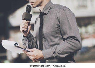 TV reporter at work. Journalist man with microphone reads questions from sheet