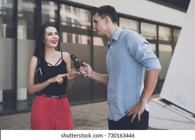 TV reporter at work. A journalist on the street holds a microphone and listens to the answer to the questions posed to the girl.