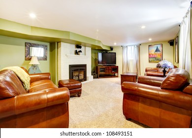 Tv room with green walls, leather sofas and fireplace and beige carpet.