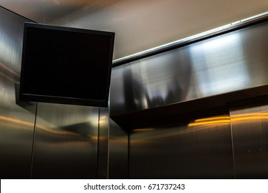 TV screen hanging in the corner of the elevator interior.