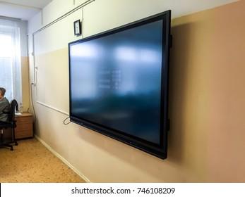 TV screen wall Big flat screen. Full HD monitor screen on wall. School computer class.High tech full hd display screens on the wall.Modern School classroom big flat screens. 4k monitor Touch screen TV