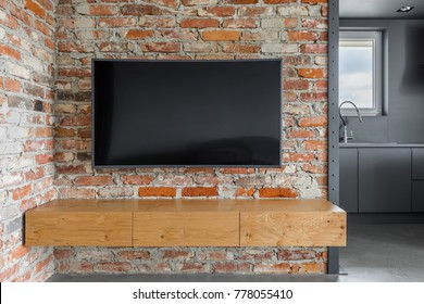 Tv screen and wooden cabinets on exposed brick wall
