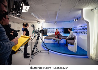 A TV show being filmed in a studio. The presenters are sitting on the studio sofa and talking to each other while the camera crew films them with film cameras. - Shutterstock ID 1836253954