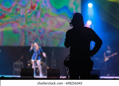 Tv show, cinema in concert background and texture.Silhouette image of the cameraman working on a blurry background in concert.