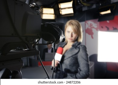 TV studio with close up on a video camera and an unrecognizable woman presenter in the background