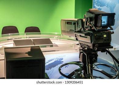 TV studio with professional camera aiming at empty seat, TV news studio with camera.