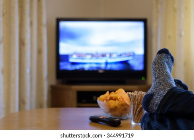 TV, television watching (refugee boat, news) with feet on the table and snacks - stock photo