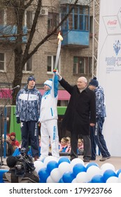 TVER, RUSSIA - MARCH 2, 2014: First lighted torch held Tver Mayor Alexander Korzin and athlete Yuri Bobrov. In Tver relay involved 100 torchbearers
