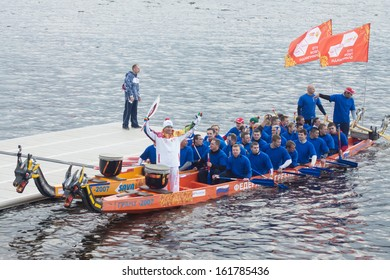 TVER, RUSSIA - OCT 11: Torchbearer Ignat Kovalev on a boat with a dragons head on October 11, 2013. The main symbol of the Olympic Games sailed down the Volga river, accompanied by two hundred vessels