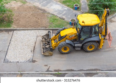 TVER, RUSSIA - SEPTEMBER 9, 2015: Excavator filled with broken asphalt in the yard near the pit filled with gravel