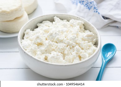 Tvorog, farmers cheese, curd cheese or cottage cheese in white bowl on white wooden table, closeup view. Rich in calcium healthy food