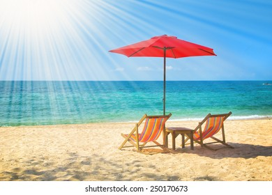Tw lounge chairs and a sunshade umbrella on the beach