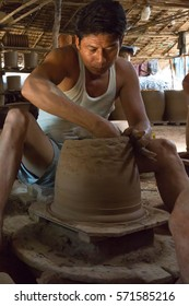 TWANTE, MYANMAR - NOVEMBER 27, 2016: A craftperson artist is creating a earthware vase. This establishment provides a large part of the region earthware containers