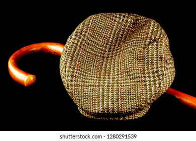 Tweed cap and walking stick isolated on a black background