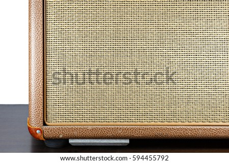 Tweed guitar amp sitting on a dark wood floor with pure white background.
