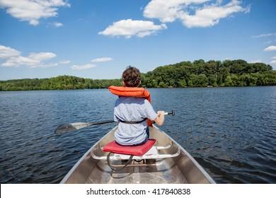 Tween boy rowing in a boat with oar on a lake in summertime