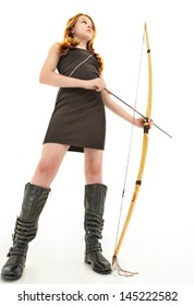 Tween girl in black dress and boots holding a handmade bow and arrow over white background.