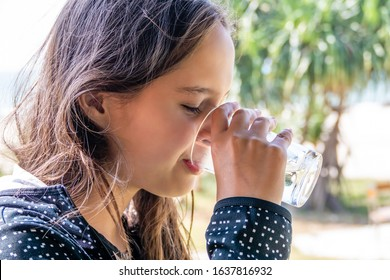 Tween girl drinks water with blurred beach background