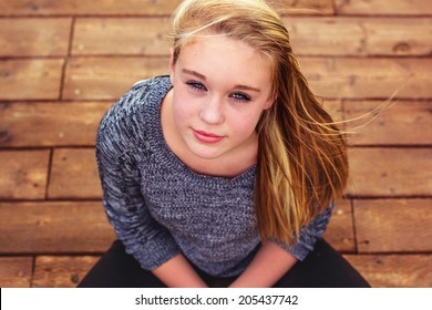 Tween girl lying on a wooden bridge at the park -- image taken outdoors at Rancho San Rafael Park in Reno, Nevada, USA