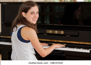 Tween girl playing the piano with hands on keyboard