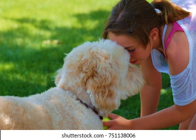 A tween girl with a pony tail nose to nose with her Goldendoodle dog on a summer day.
