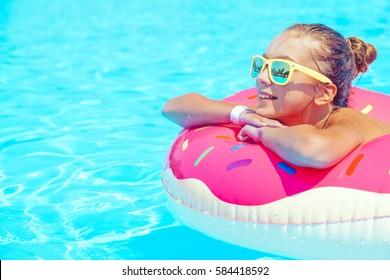 Tween girl relaxing on the inflatable ring in resort pool in Thailand