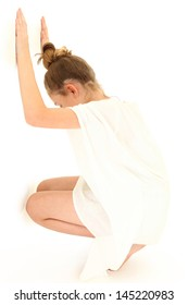 Tween girl in white dress against a white wall alone.