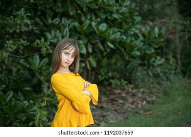 Tween Girl in Yellow Gold Outside in Greenery with Attitude