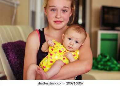 Tween year old girl holding her 3 month old baby sister -- image taken in Reno, Nevada, USA