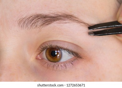 tweezers with eyebrows on a brown eyed girl