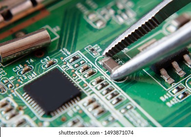 tweezers holding chip on computer circuit board, assembling a circuit board macro