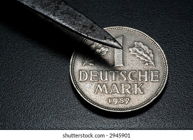 tweezers picking up the german mark (coin)