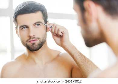 Tweezing his eyebrows. Handsome young man tweezing his eyebrows and looking at himself while standing in front of the mirror