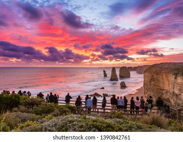 Twelve Apostles, Great Ocean Road, Australia – April 18, 2019: People looking at the stunning sunset at Twelve Apostles, limestone pinnacles formed by erosion of the cliffs by Southern Ocean.