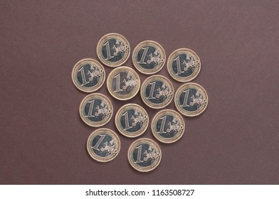 twelve coins in one Euro on a dark background top view