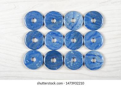 Twelve dumortierite round donut-shaped stones are stowed three rows. Four pieces in each one. Top view.