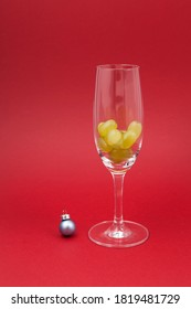 Twelve grapes in a glass for sparkling wine cava. Selective focus, red background, copy space. Spanish traditional to eat twelve 12 berries for good luck at midnigth. Christmas New Year composition.