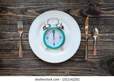 Twelve hour intermittent fasting time concept with clock on plate over a rustic wooden table / background. Top view.
