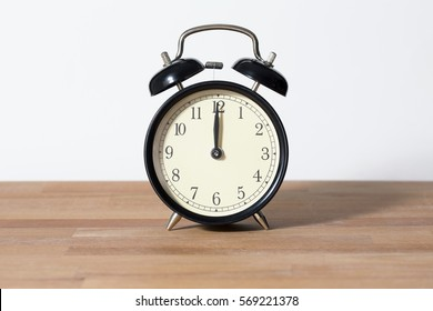 It is twelve o'clock. The time is 12:00 am or pm and noon or midnight. A retro clock isolated on wooden table. White background. Copy space and cut.