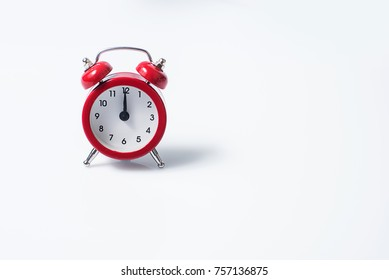 Twelve is on a small red clock, isolated on white