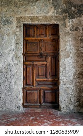 A twelve panel rustic wooden door is found at one end of the convent cloister of Mission Concepcion near San Antonio, Texas, established in 1731 by Spanish Franciscans.