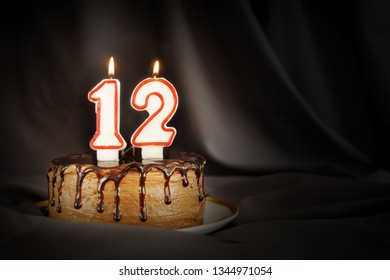 Twelve years anniversary. Birthday chocolate cake with white burning candles in the form of number Twelve. Dark background with black cloth