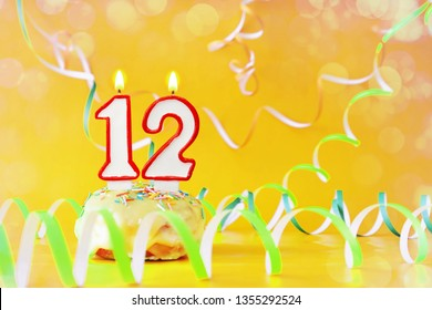 Twelve years birthday. Cupcake with burning candles in the form of number 12. Bright yellow background with copy space