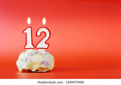 Twelve years birthday. Cupcake with white burning candle in the form of number 12. Vivid red background with copy space