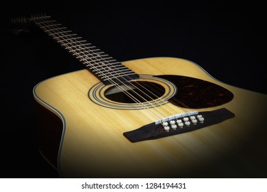 Twelve-string acoustic guitar and beautiful light rims, frets and body shape, isolated on a black background